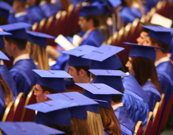 graduates in blue caps and gowns at a graduation ceremony