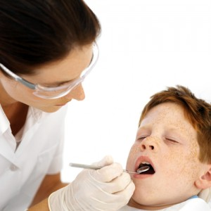 Boy in dentist chair having his teeth examined